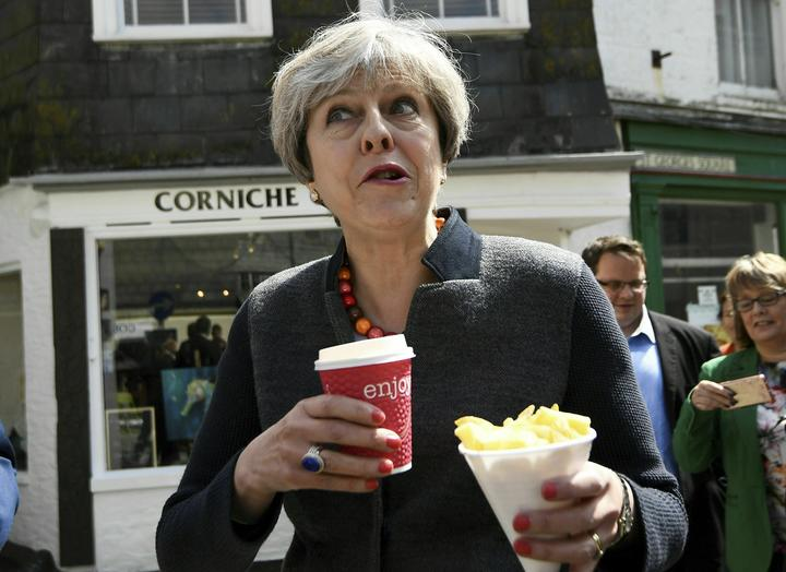 FILE - In this May 2, 2017 file photo Britain's Prime Minister Theresa May having some chips while on a walkabout during a election campaign stop in Mevagissey, Cornwall.