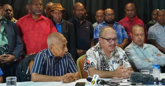 Papua New Guinea Prime Minister Peter O'Neill (seated, centre) announces his resignation, handing over to Sir Julius Chan (seated, left) 27 May 2019