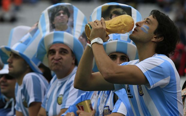 An Argentinian fan holds a replica of the world cup trophy at The Corinthians Arena in Sao Paulo.