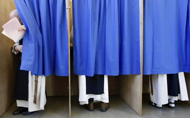 Monks from the Saint Sixtus Trappist Abbey cast their votes behind curtains at a polling station in Westvleteren, Belgium, Sunday, May 26, 2019.