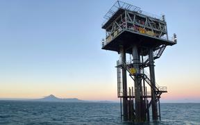Southern Star Oil rig platform at sunset with  Mt Taranaki in the background