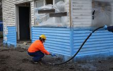 A water-proof membrane designed to protect flood-prone houses is sprayed on.