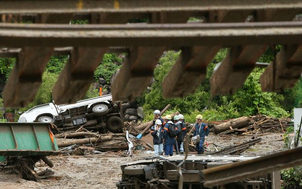 Workers at the site of a landslide caused by the typhoon at Nagiso town in Nagano prefecture.