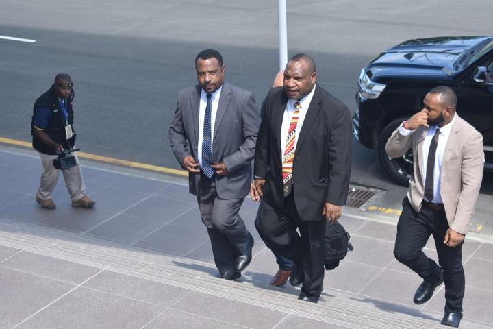 James Marape (centre in black suit) walks back to parliament after being sworn in as prime minister of Papua New Guinea, 30 May 2019.