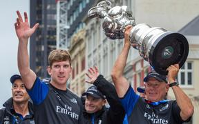 Team New Zealand helmsman Peter Burling and Team New Zealand Boss Grant Dalton hold aloft the Americas Cup during the Emirates Team New Zealand victory Parade held in Auckland in July 2017.