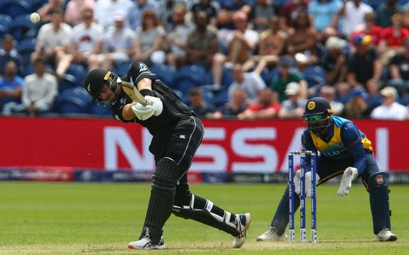 New Zealand's Martin Guptill (L) is watched by Sri Lanka's wicketkeeper Kusal Perera as he hits a six during the 2019 Cricket World Cup group stage match between New Zealand and Sri Lanka at Sophia Gardens stadium in Cardiff.