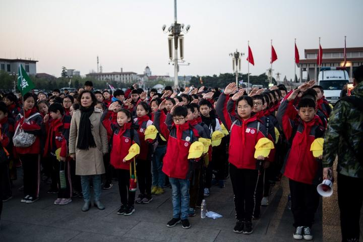 In this picture taken on April 1, 2019, school students sing the national anthem at Tiananmen square in Beijing. - Thirty years after the crackdown on Tiananmen protesters, the tanks that lined Beijing's central avenue have been replaced by countless surveillance cameras