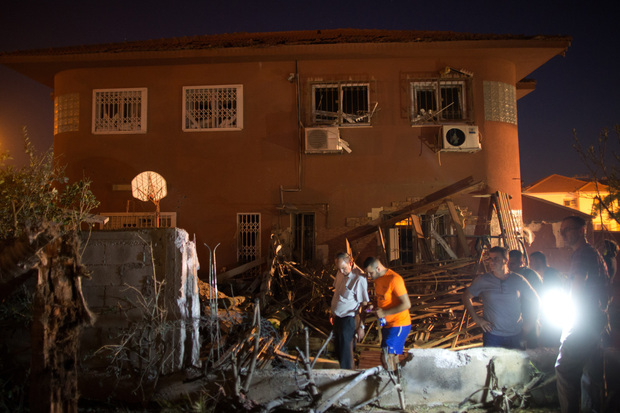 Israelis inspect damage to a house in Beer Sheva hit by a rocket fired from Gaza