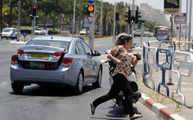 A woman runs for cover during a rocket attack in the Israeli city of Ashdod.