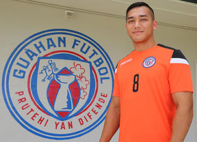 Mark Chargualaf poses alongside the new Guam Football national team badge.