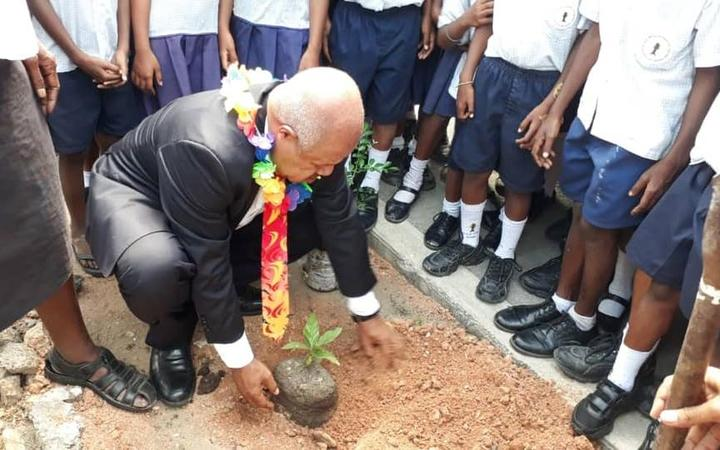 The governor of Papua New Guinea's National Capital District, Powes Parkop, plants a tree at the start of an initiative to plant one million trees in Port Moresby.