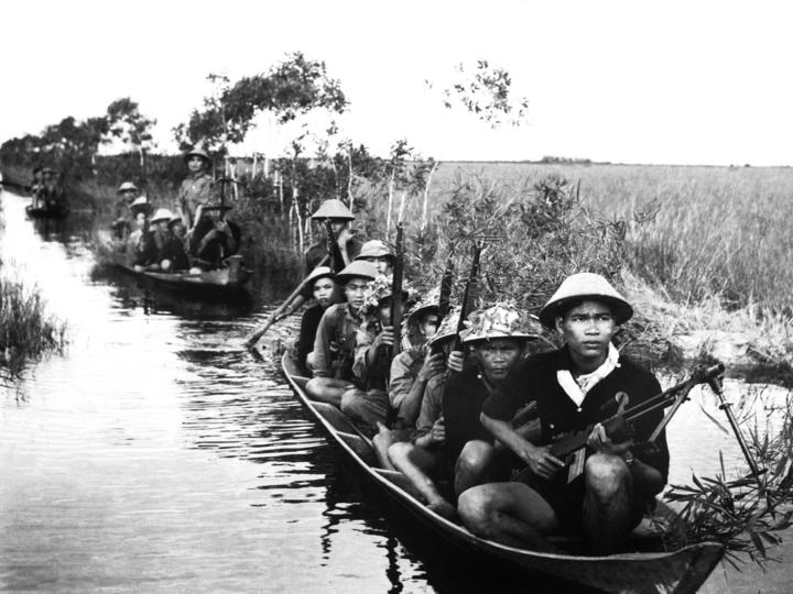 Viet Cong fighters crossing a river during the Vietnam War.