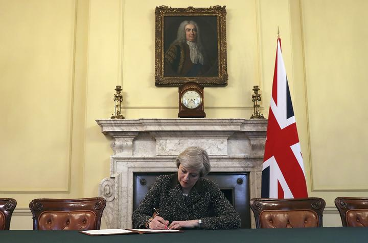 FILE - In this Tuesday March 28, 2017 file photo Britain's Prime Minister Theresa May, sitting below a painting of Britain's first Prime Minister Robert Walpole,