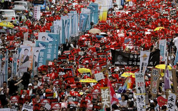Protesters against the extradition law march along a downtown street in Hong Kong Sunday, June 9, 2019.