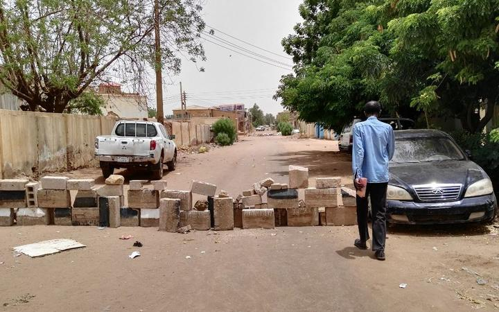 A Sudanese man walks towards a barricade made of bricks to block a street for cars in Khartoum's twin city Omdurman on the first day of a civil disobedience campaign across Sudan on June 9, 2019. )