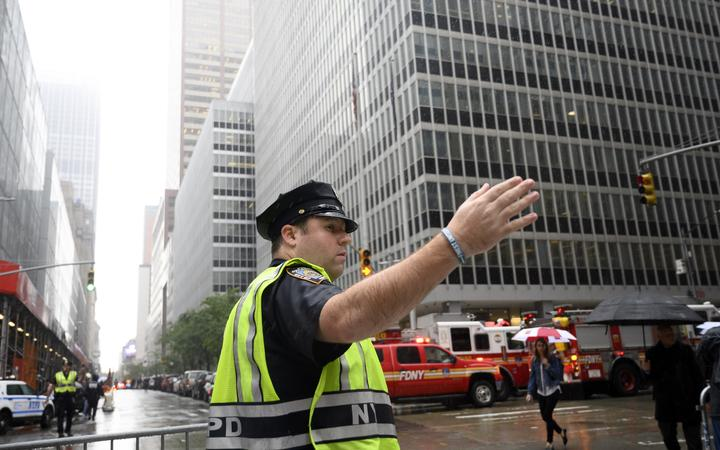 A policeman standing near fire trucks after a helicopter crash-landed on top of a building in midtown Manhattan in New York on 10 June 2019.