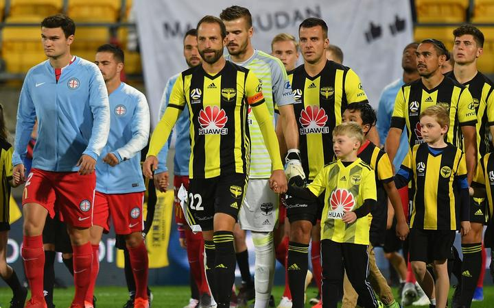 Andrew Durante leads the Phoenix onto the field against Melbourne City.