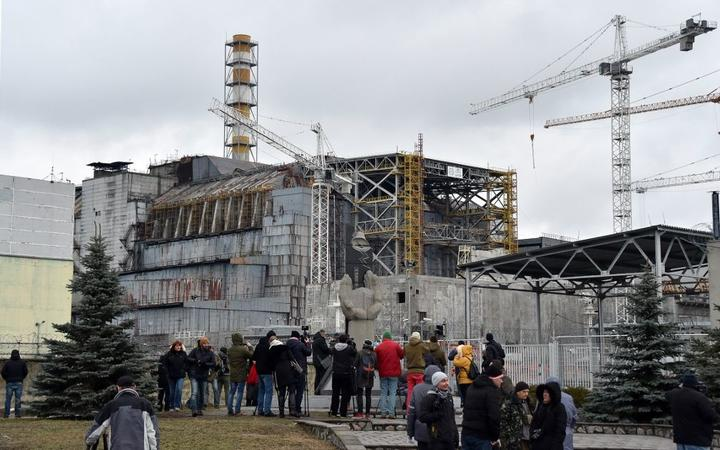 Visitors and journalists gather in front of a shelter and containment area built over the destroyed fourth block of Chernobyl's old nuclear power plant on December 14, 2015 in Chernobyl. -