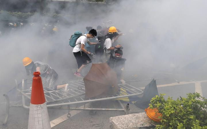 Protesters react to a cloud of tear gas near the Legislative Council in Hong Kong, Wednesday, June 12, 2019.