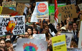This picture taken on March 15, 2019 shows students raising placards during a protest highlighting inadequate progress to address climate change, in Sydney.
