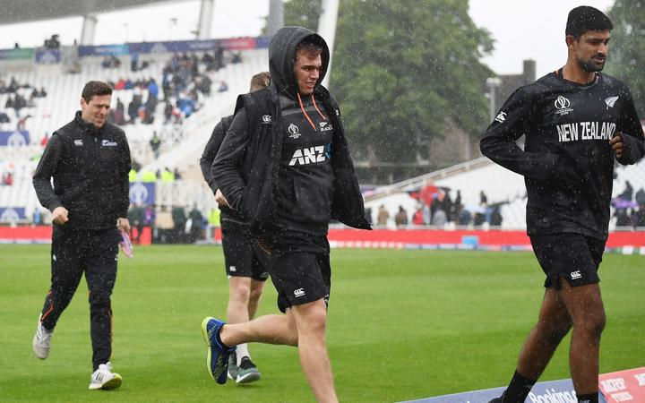 Tom Latham and Ish Sodhi run from the rain showers as the Black Caps' World Cup game against India is called off.