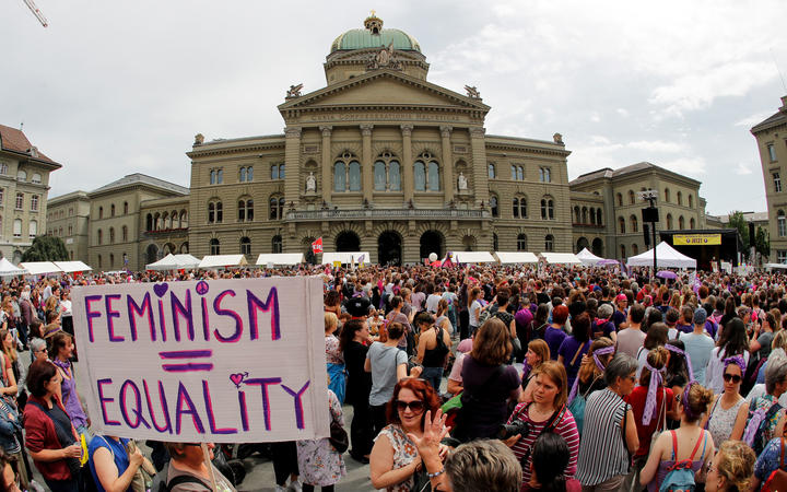 "A woman holds a sign reading ""Feminism = Equality"" as she takes part in a nation-wide women's strike for wage parity outside the federal palace in Switzerland."