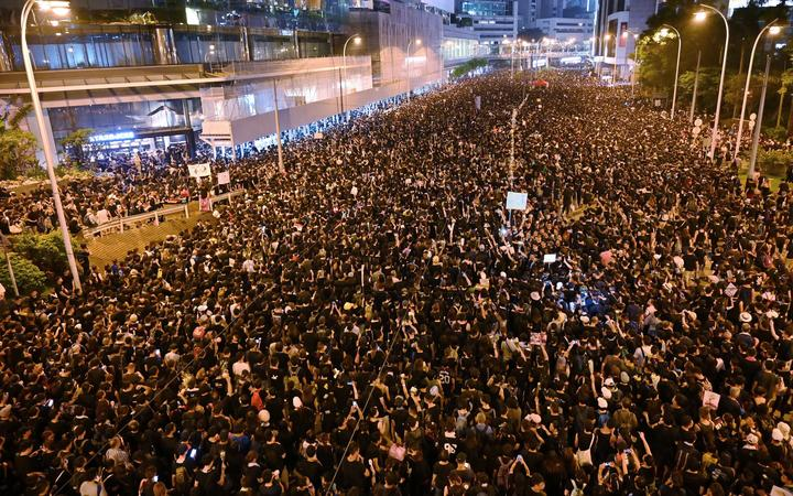 Thousands of protesters dressed in black take part in a rally against a controversial extradition law proposal in Hong Kong .