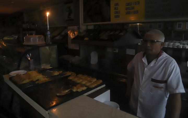 A man working by candlelight in a Buenos Aires bakery during a country-wide power cut on 16 June 2019.