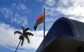 The Vanuatu flag flying above the buildings of the public broadcaster VBTC