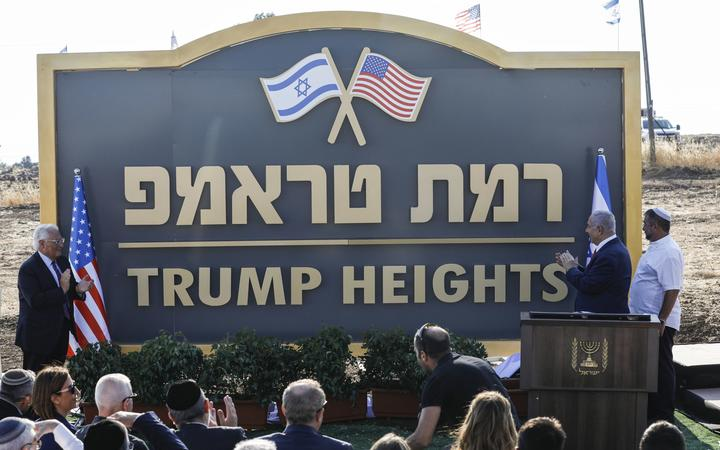 "Israeli Prime Minister Benjamin Netanyahu (second from right) and US Ambassador to Israel David Friedman (left) applaud after unveiling the place-name sign for the new settlement of ""Trump Heights"" in the Golan Heights"
