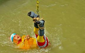 "In this photo taken on June 16, 2019 Indian stuntman Chanchal Lahiri, known by his stage name ""Jadugar Mandrake"", is lowered into the Ganges river, while tied up with steel chains and ropes, in Kolkata."