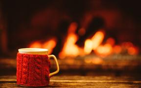Cup of hot drink in front of warm fireplace.