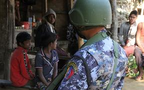 A Myanmar border guard policeman stands near a group of Rohingya Muslims at a small store in a village during a government-organized visit for journalists in Buthidaung townships in the restive Rakhine state on January 25, 2019.