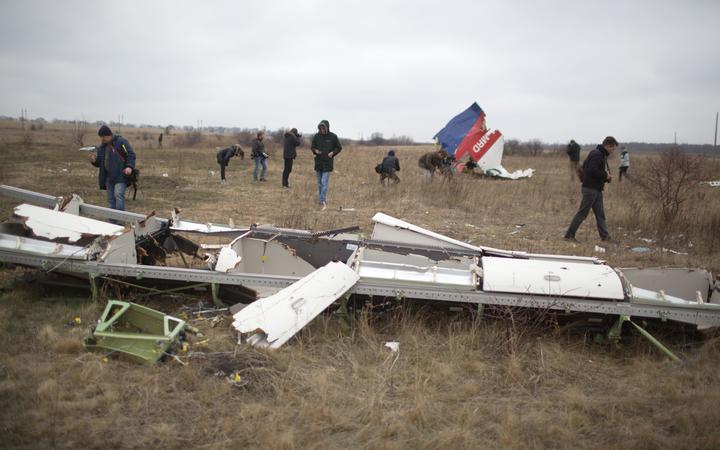Journalists look at parts of the Malaysia Airlines plane Flight MH17 as Dutch investigators (unseen) arrive at the crash site near the Grabove village in eastern Ukraine on November 11, 2014