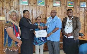 Vanuatu's Special Envoy for West Papua, Lora Lini, hands over the United Liberation Movement for West Papua's application for full membership in the Melanesian Spearhead group to the MSG Deputy Director General Peter Eafeare. ULMWP executive member Paula Makabory (middle) observes.