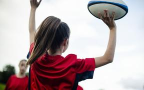 Female rugby player jumping with a ball
