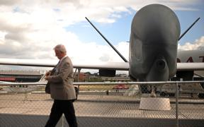 A visitor walks past a Northrop Grumman RQ-4 Global Hawk unmanned aircraft at the Farnborough International Airshow in Hampshire, southern England, on July 22, 2010.