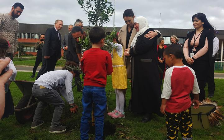 Prime Minister Jacinda Ardern plants a pōhutukawa tree in memory of the Christchurch terror attack victims, with members of one of the families, refugees who are being resettled in New Zealand.