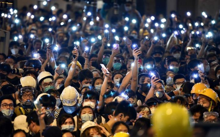 Protesters hold up their mobile phones as they gather outside the police headquarters in Hong Kong on June 21, 2019.