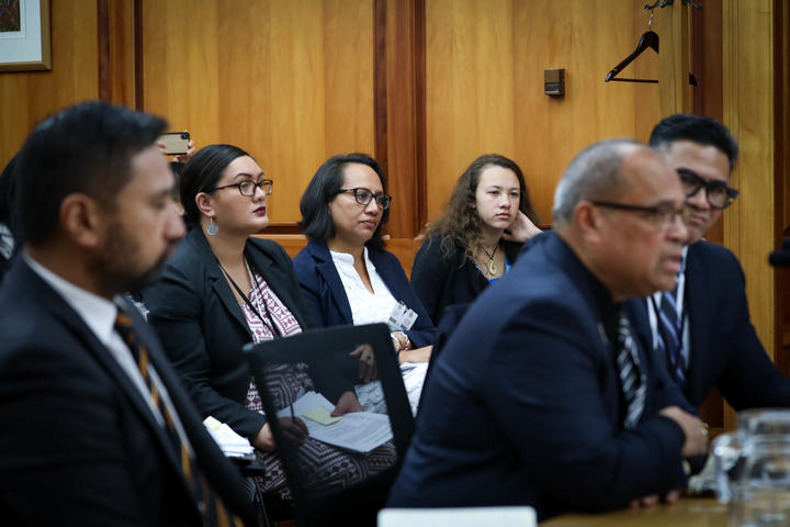 Journalist Esther Pavihi from Niue and journalist Tiana Haxton from the Cook Islands observe the Minister for Pacific Peoples at select committee in Wellington.