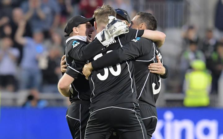 New Zealand players celebrate with New Zealand's James Neesham (C) after he takes the final wicket of West Indies' Carlos Brathwaite during the 2019 Cricket World Cup group stage match between West Indies and New Zealand at Old Trafford in Manchester.