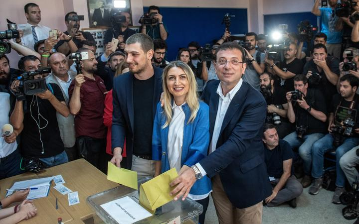 Istanbul mayoral candidate of the main opposition Republican People's Party (CHP) Ekrem Imamoglu, right, casts his vote with wife Dilek Imamoglu, centre, and son Semih Imamoglu, left.