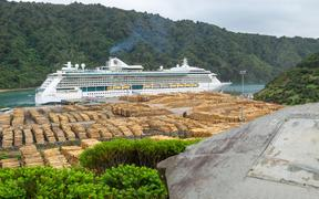 PICTON NEW ZEALAND- OCTOBER 2 2018; Radiance of Seas huge passenger cruise ship moored at Shakespeares Bay Wharf with logs stcked and waiting to be shipped.