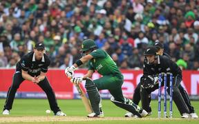 Pakistan's Babar Azam is watched by Black Caps James Neesham and Tom Latham as he plays a shot during the 2019 Cricket World Cup group stage match.