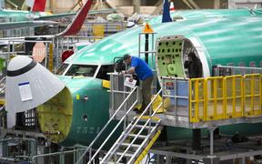 (FILES) In this file photo taken on March 27, 2019 Employees work on Boeing 737 MAX airplanes at the Boeing Renton Factory in Renton, Washington.