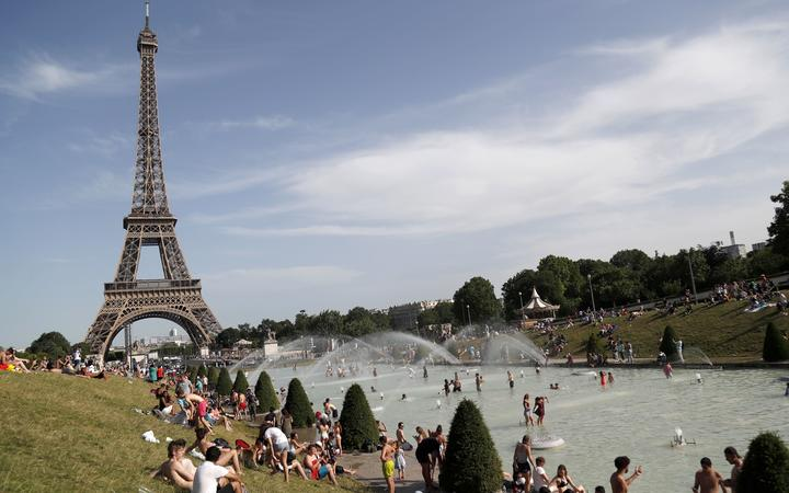 People bathe in the Trocadero Fountain near the Eiffel Tower in Paris during a heatwave on June 28, 2019. )