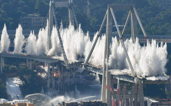Explosive charges blow up the eastern pylons of Genoa's Morandi motorway bridge on June 28, 2019 in Genoa. -
