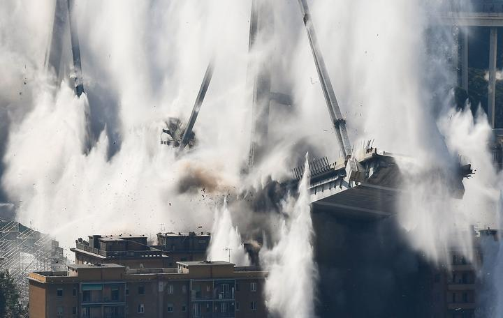 The bridge's deck collapses in a cloud of smoke and water after explosive charges blew up the eastern pylons of Genoa's Morandi motorway bridge on June 28, 2019 in Genoa.