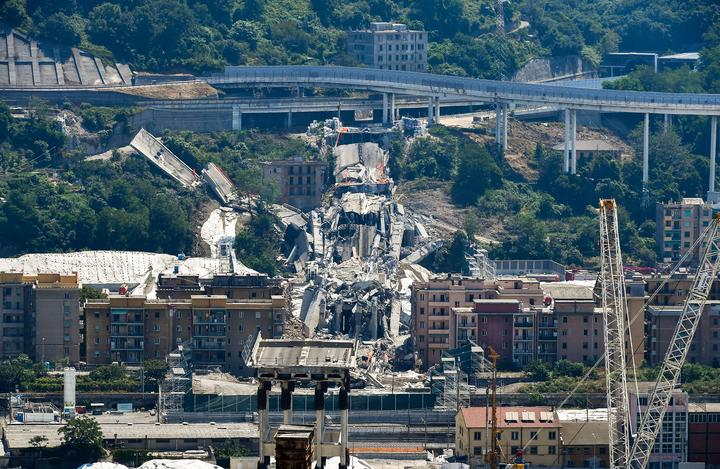 A general view shows the bridges' deck debris and rubble (Rear C) among evacuated buildings after explosive charges blew up the eastern pylons of Genoa's Morandi motorway bridge on June 28, 2019 in Genoa.