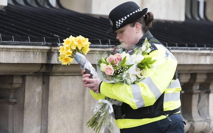A police officer with flowers the day after Terror attack in the heart of London, Westminster. London.